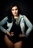 Contemporary studio portrait of a young woman in a black bodysuit, denim jacket and silver necklaces looking at the camera by Vancouver portrait photographer Angela McConnell