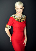 Portrait of an older woman in a red dress with leopard trim and short blonde hair smiling at the camera