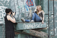 Behind the scenes image of a photographer during an outdoor natural light photoshoot session in an alleyway with graffiti