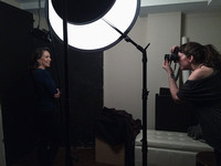 Behind the scenes photo of a photographer taking pictures of a head shot client in a home studio
