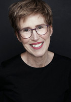Studio headshot of a woman with glasses smiling at the camera
