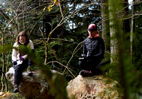 Two women sitting on rocks surrounded by trees journaling during a life coach and fitness retreat by Vancouver workshop and retreat photographer Angela McConnell