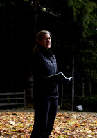 Women in a winter clothing standing in a clearing with autumn leaves on the ground during an outdoor life coaching session at a self care and fitness retreat by Vancouver workshop and retreat photogra