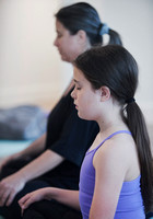 Image of a young girl seated in meditation next to her mother during a mother and daughter workshop by Vancouver workshop and retreat photographer Angela McConnell