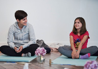A mother smiles at her daughter as they sit on yoga mats during an exercise at a mother and daughter workshop by Vancouver workshop and retreat photographer Angela McConnell