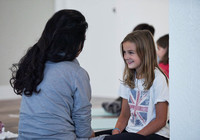A young girl smiles at her mother as she sits directly across from her during an exercise at a mother and daughter workshop by Vancouver workshop and retreat photographer Angela McConnell