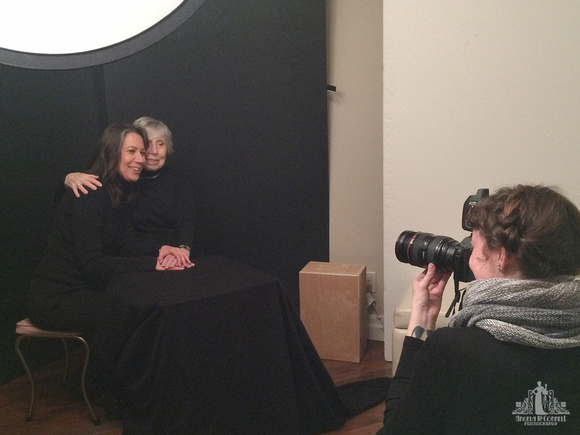 Behind the scenes image of a photographer during a photoshoot in studio with an adult mother and daughter