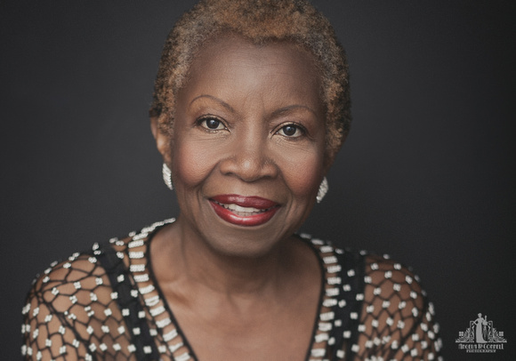 Contemporary studio portrait of an older black woman with natural hair and red lipstick smiling directly at the camera by Vancouver portrait photographer Angela McConnell
