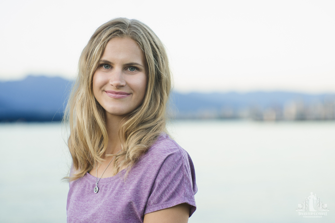 Head shot of a young woman in a purple t-shirt with English Bay BC in the background