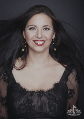Portrait of a woman in a black lace dress smiling at the camera