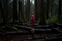Natural light portrait of a young woman in a red dress and flower crown in the Pacific Spirit Park in Vancouver BC