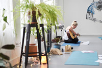 A young woman sitting on a yoga mat playing a guitar and singing surrounded by plants in a yoga studio at a mother and daughter workshop by Vancouver workshop and retreat photographer Angela McConnell